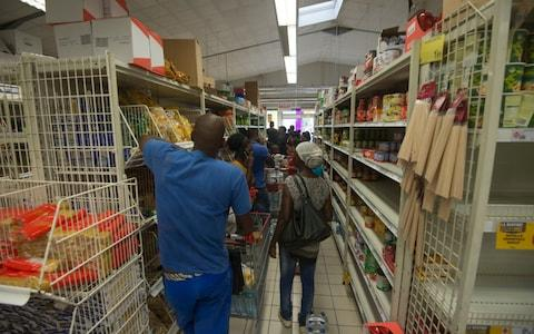 People queue at a supermarket as they buy goods as part of preparations ahead of the arrival of Hurricane Irma in the French overseas island of Guadeloupe - Credit: AFP