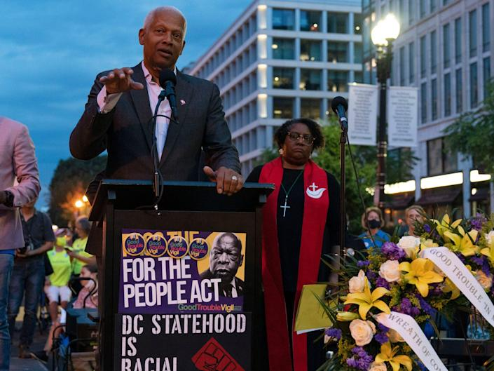 Rep. Hank Johnson speaks in support of voting rights behind platform at rally.