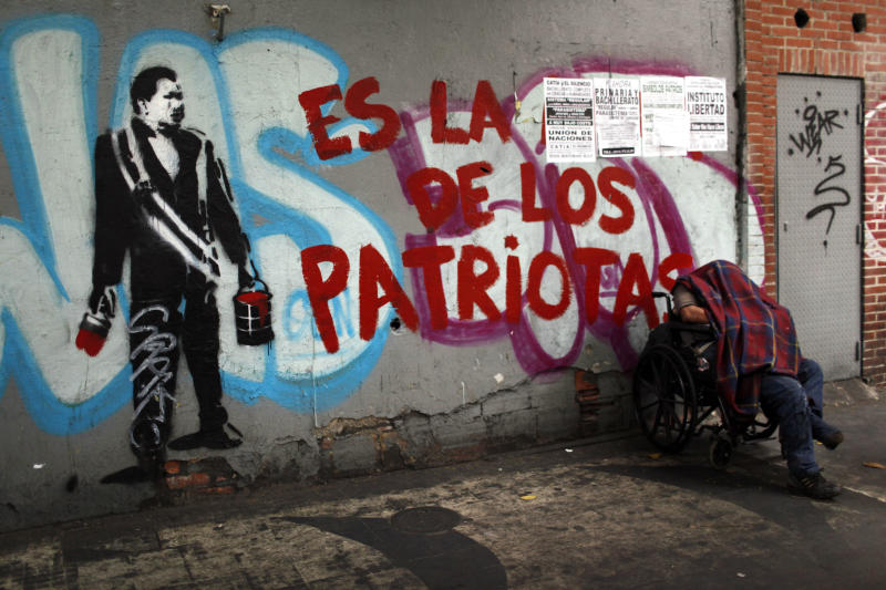 """A man rests next to a graffiti that reads in Spanish, """"Is of the patriots,"""" next to a stencil mural of Venezuela's late President Hugo Chavez in downtown Caracas, Venezuela, Thursday, March 14, 2013. Venezuela's acting president said Wednesday that it is highly unlikely Hugo Chavez will be embalmed for permanent viewing because the decision to do so was made too late and the socialist leader's body was not properly prepared on time. Chavez died on March 5. The decision to preserve his body permanently was announced two days later. (AP Photo/Rodrigo Abd)"""