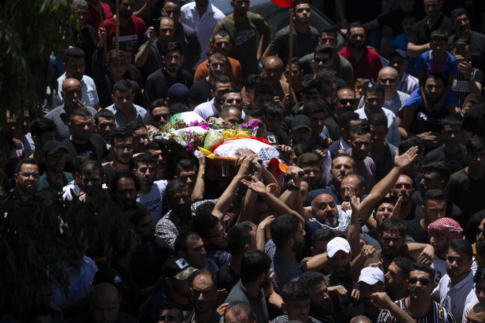 Palestinians carry the body of Mohammed al-Alami, 12, during his funeral in the village of Beit Ummar, near the West Bank city of Hebron, Thursday, July 29, 2021. Villagers say the boy was fatally shot by Israeli troops while traveling with his father in a car. The Israeli military has launched an investigation into the shooting. (AP Photo/Majdi Mohammed)