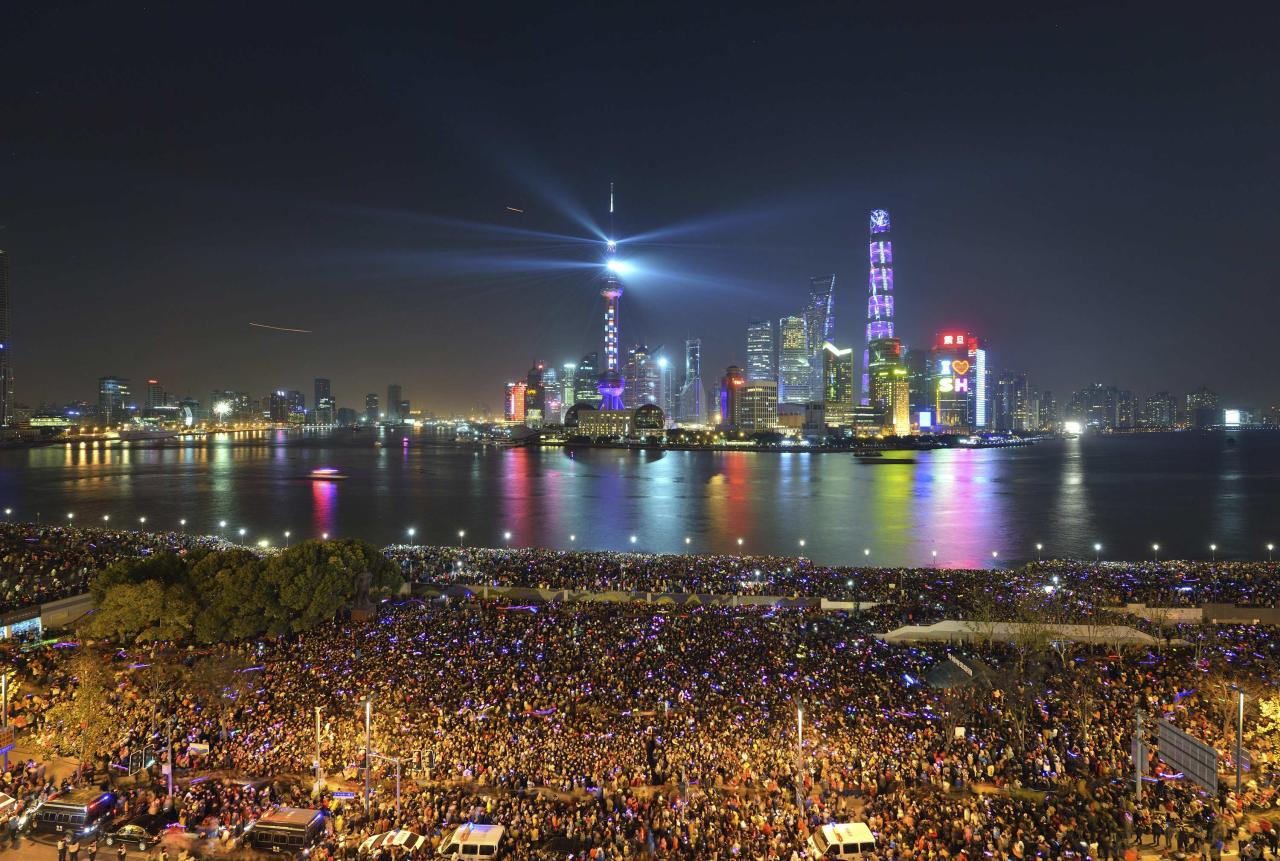 People watch a light show before a stampede incident occurred at the New Year's celebration on the Bund, a waterfront area in central Shanghai December 31, 2014. The stampede killed at least 36 people, authorities said, possibly caused by people rushing to pick up fake money thrown from a building overlooking the city's famous Bund waterfront district. Picture taken December 31, 2014. REUTERS/Stringer (CHINA - Tags: DISASTER SOCIETY ANNIVERSARY) CHINA OUT. NO COMMERCIAL OR EDITORIAL SALES IN CHINA