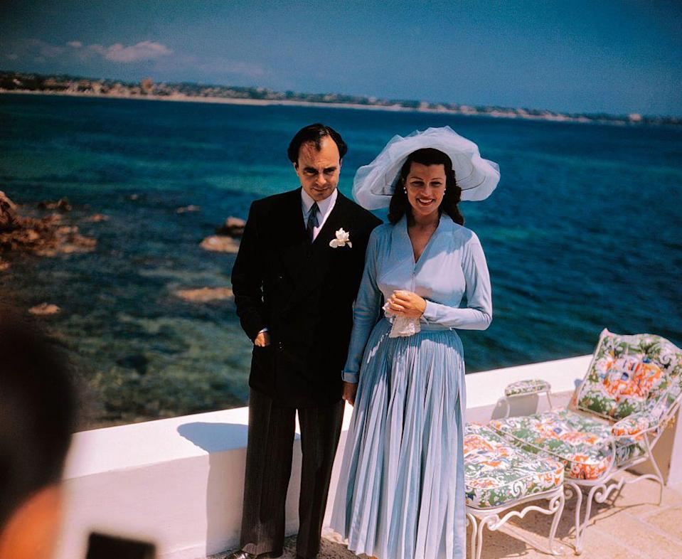<p>After her marriage to director Orson Welles ended, '40s film star Rita Hayworth caught the attention of Prince Aly Khan. The two married in 1949 on the French Rivera in a highly publicized ceremony. Rita chose a light blue, pleated dress and matching wide brimmed hat for the occasion — a style that was soon replicated by many across the United States. </p>
