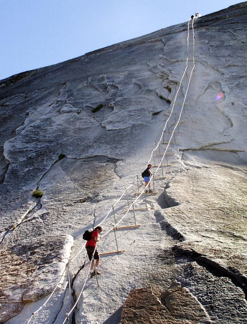 FILE - In this June 6, 2004 file photo, hikers descend the cable route after climbing to the summit of Half Dome, in Yosemite National Park. The trail of dirt and hundreds of feet of twisted metal cables might not immediately conjure an image of something worthy of historical preservation. But when the trail leads to the iconic Half Dome in Yosemite National Park and the cables allow armchair wilderness lovers to ascend the once-inaccessible granite monolith, the significance becomes enough for listing on the National Register of Historic Places. While such a move might go unnoticed, as it did last month, the timing and significance are critical as Half Dome hikers and wilderness advocates await the park's final assessment of a plan to permanently limit access to a place on many outdoor lovers' bucket lists.  (AP Photo/Robert F. Bukaty)