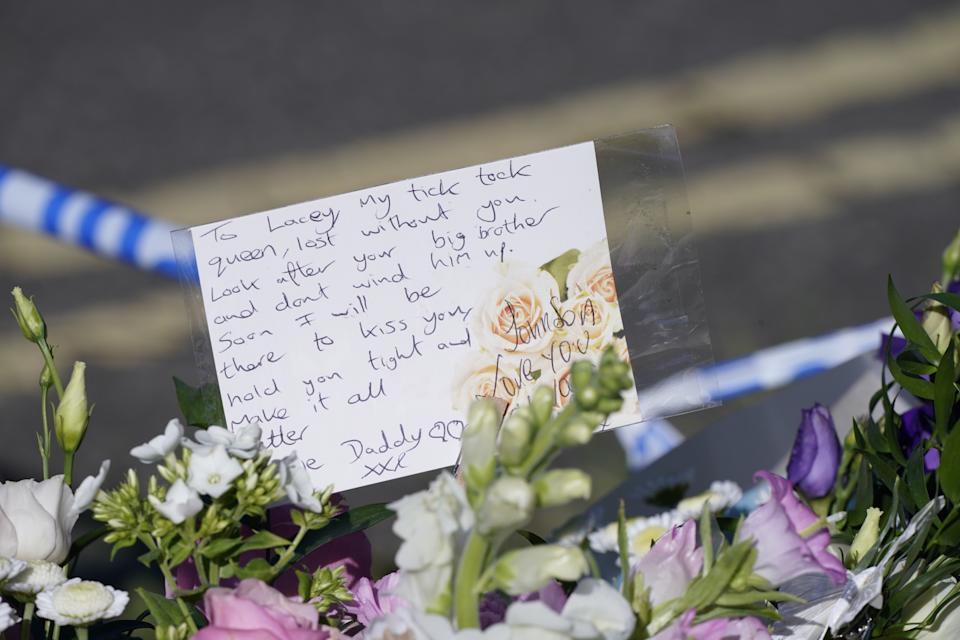Messages left by the father to one of the victims on bouquets of flowers at the scene in Chandos Crescent, Killamarsh, near Sheffield, where four people were found dead at a house on Sunday. Derbyshire Police said a man is in police custody and they are not looking for anyone else in connection with the deaths. Picture date: Monday September 20, 2021.