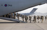 """Photo issued on Saturday Aug. 28, 2021 by Britain's Ministry of Defence (MoD) showing UK military personnel boarding a A400M aircraft departing Kabul, Afghanistan. Britain ended its evacuation flights Saturday, though Prime Minister Boris Johnson promised to """"shift heaven and earth"""" to get more of those at risk from the Taliban to Britain by other means. Britain's ambassador to Afghanistan, Laurie Bristow, said in a video from Kabul airport and posted on Twitter that it was """"time to close this phase of the operation now."""" (Jonathan Gifford/MoD via AP)"""