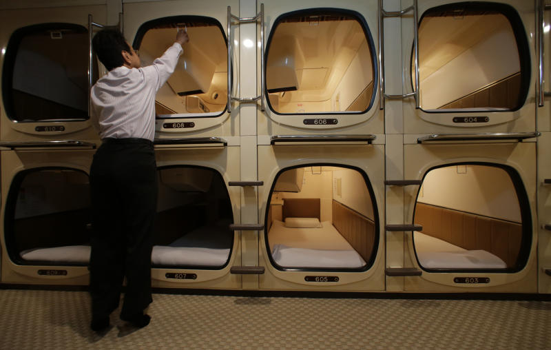 In this Monday, Oct. 29, 2012 photo, manager Akiyoshi Kaneko stands by the rooms at the Capsule & Sauna Century Shibuya in Tokyo. The capsule concept has been around for at least 30 years, starting out as lodging for businessmen working or partying late who missed the last train home and needed a cheap place to crash. But budget travelers and other folks curious about a unique lodging experience use them too. (AP Photo/Shizuo Kambayashi)