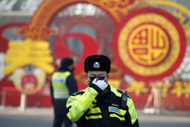 A traffic policeman adjusts his mask on a street in Beijing (Andy Wong/AP)