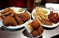"""<p>The South is known for its fried chicken and its <a href=""""https://www.thedailymeal.com/eat/every-regional-barbecue-style-explained?referrer=yahoo&category=beauty_food&include_utm=1&utm_medium=referral&utm_source=yahoo&utm_campaign=feed"""" rel=""""nofollow noopener"""" target=""""_blank"""" data-ylk=""""slk:barbecue"""" class=""""link rapid-noclick-resp"""">barbecue</a>, but it can be hard to decide between the two. Well, if you're at Bar-B-Q King in Charlotte, North Carolina, you don't have to. This joint's signature menu item is fried chicken soaked in barbecue sauce with wonderfully crispy skin and a killer sauce. (Be sure to order more on the side for dipping.) If you're not feeling chicken, patrons of this old-school drive-in also rave about the barbecue pulled pork, homemade hush puppies and onion rings.</p>"""