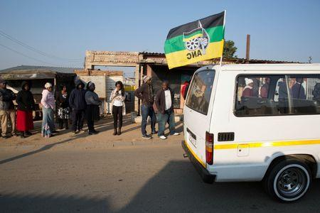 A taxi carrying the flag of the ruling African National Congress (ANC) party drives past locals queueing  to cast their votes during the Local Government elections in Diepsloot township, north of Johannesburg, South Africa