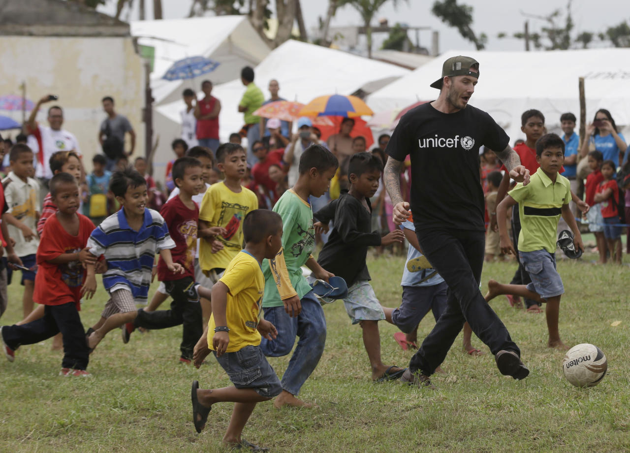FILE - In this Friday, Feb. 14, 2014 file photo, David Beckham plays soccer with young typhoon-survivors during his visit to typhoon-ravaged Tanauan township, Leyte province in central Philippines. Beckham turns 40 on Saturday May 2, but since retiring, England's former captain continues to prosper off the field, where his multi-faceted life centers on celebrity and fashion, but also ambassadorial roles and an ambitious project to create a Miami team in the increasingly popular Major League Soccer. (AP Photo/Bullit Marquez, file)