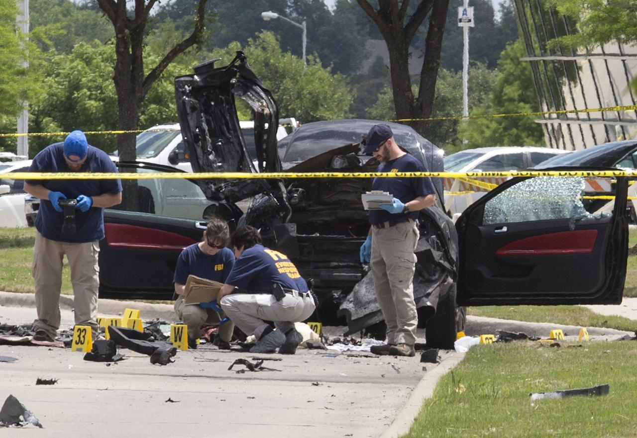 Local police and FBI investigators collect evidence and survey the scene where two gunmen were shot dead, after their bodies were removed in Garland, Texas May 4, 2015. Texas police shot dead two gunmen who opened fire on Sunday outside an exhibit of caricatures of the Prophet Mohammad that was organized by a group described as anti-Islamic and billed as a free-speech event. REUTERS/Laura Buckman