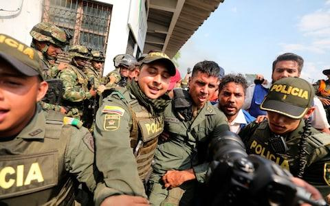 Colombian police escorting a Venezuelan soldier who surrendered at the Simon Bolivar international bridge - Credit: AP