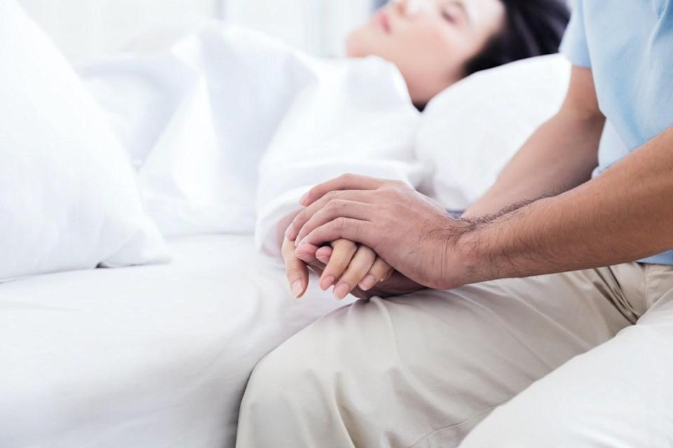 Man holding hand of a sick loved one in hospital