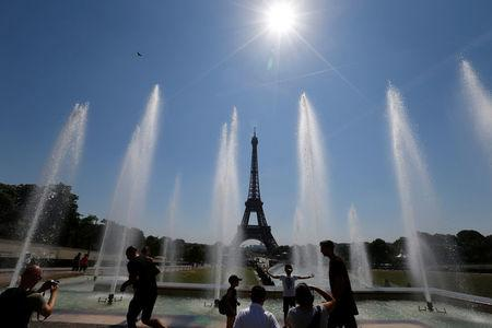 People cool off in the fountains across from the Eiffel Tower as a heatwave with high temperatures continues in Paris, France, August 3, 2018. REUTERS/Regis Duvignau