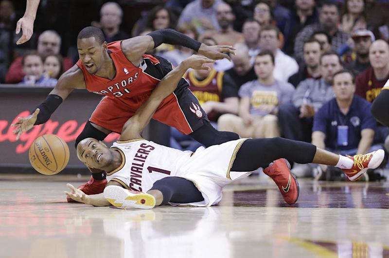 Cleveland Cavaliers' Jarrett Jack (1) and Toronto Raptors' Terrence Ross (31) battle for a loose ball during the second quarter of an NBA basketball game, Tuesday, Feb. 25, 2014, in Cleveland. (AP Photo/Tony Dejak)