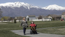 FILE - In this on April 14, 2020, file photo, Jodi Hansen walks with her son Jacob Hansen near their home in Eagle Mountain, Utah. Utah overhauled crisis guidelines Thursday, Aug. 20, 2020, that could have put people with disabilities at the back of the line if hospitals become overwhelmed during the coronavirus pandemic, adopting a new plan that federal officials said should serve as a national model for removing bias from life-or-death decisions. In Utah, the complaint was filed on behalf of Hansen, who has cystic fibrosis that affects his lungs and uses a wheelchair due to cerebral palsy. (AP Photo/Rick Bowmer, File)