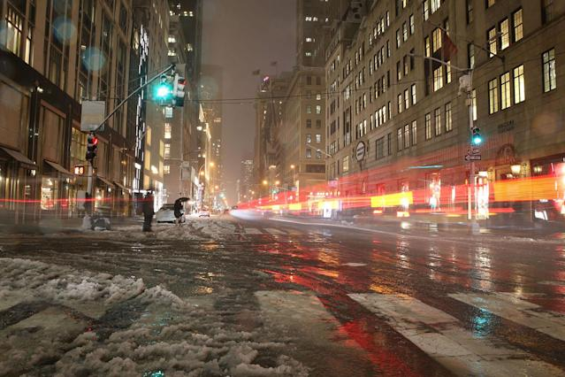 <p>In a photo taken with a long exposure, vehicles pass as pedestrians cross Fifth Avenue in midtown Manhattan during a storm in New York City on March 7, 2018. (Photo: Gordon Donovan/Yahoo News) </p>