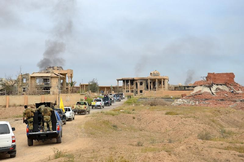 Iraqi security forces and Shiite fighters from the Popular Mobilisation units drive down a road surrounded by damaged houses, in the northern Iraqi city of Tikrit on March 31, 2015 (AFP Photo/Younis Al-Bayati)