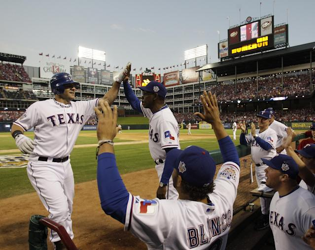 FILE - In this Oct. 30, 2010 file photo, Texas Rangers' Mitch Moreland, left, is congratulated by Rangers manager Ron Washington after hitting a three-run home run during the second inning of Game 3 of baseball's World Series against the San Francisco Giants, in Arlington, Texas. A perfect game, MLB's first-ever interleague game and consecutive World Series for the Texas Rangers. Those are some of the highlights at their home stadium, which Friday, April 11, 2014, marks the 20th anniversary of its first regular-season game.(AP Photo/David J. Phillip, File)