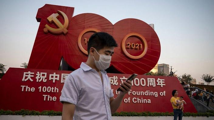 People taking pictures in front of a sign celebrating the 100th anniversary of the founding of the Communist Party of China in Shanghai.