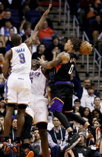 Phoenix Suns' Michael Beasley (0) has his shot blocked by Oklahoma City Thunder's Kendrick Perkins, center, as Serge Ibaka (9), of the Congo, comes in to defend during the first half in an NBA basketball game, Sunday, Feb. 10, 2013, in Phoenix. (AP Photo/Ross D. Franklin)