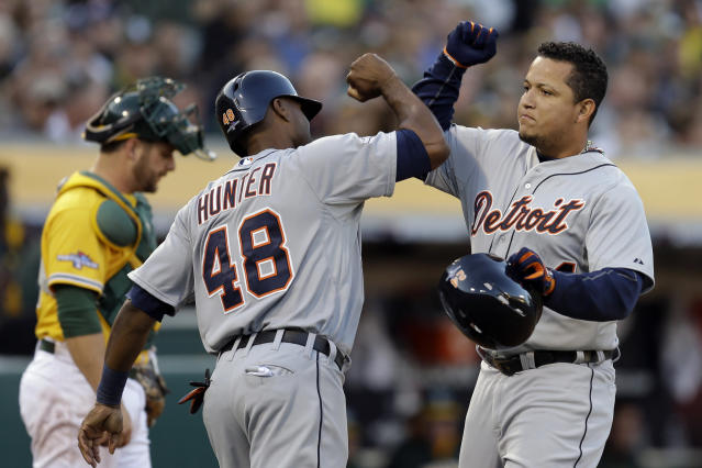 Detroit Tigers Miguel Cabrera (24) celebrates with teammate Torii Hunter (48) after he scored a two run home run that also scored Hunter in the fourth inning of Game 5 of an American League baseball division series against the Oakland Athletics in Oakland, Calif., Thursday, Oct. 10, 2013. (AP Photo/Ben Margot)