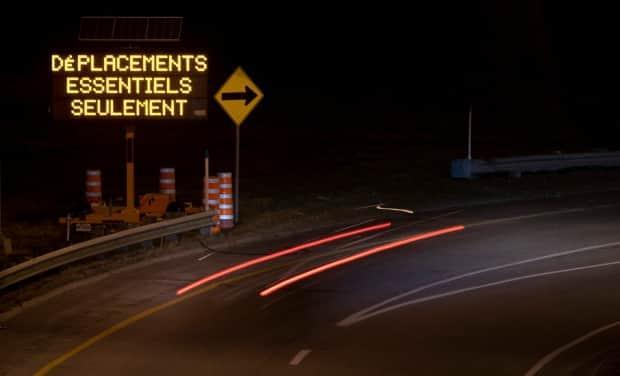 A driver passes a road sign indicating only essential travel as they enter into Gatineau, Que., from Ottawa during the hours of a provincewide curfew April 7, 2021. (Adrian Wyld/Canadian Press - image credit)