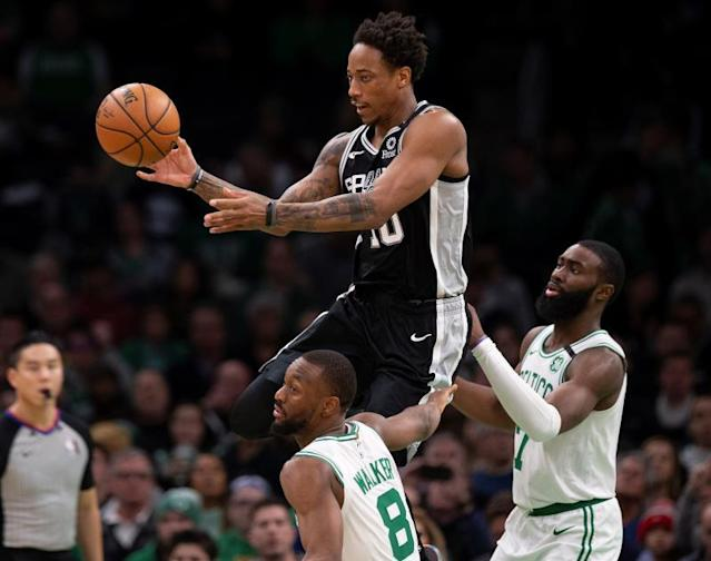 San Antonio Spurs guard DeMar DeRozan (C) leaps while making a pass over defending Boston Celtics guard Kemba Walker (L) and Boston Celtics guard Jaylen Brown (R) during the second half of the NBA basketball game between the San Antonio Spurs at Boston Celtics at the TD Garden in Boston, Massachusetts, USA, 08 January 2020. EFE/EPA/CJ GUNTHER