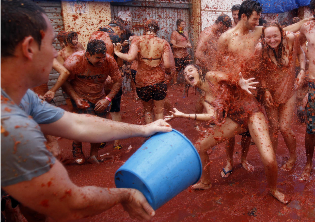 "A reveler throws tomato pulp during the annual ""Tomatina"" tomato fight fiesta in the village of Bunol, near Valencia, Spain, Wednesday, Aug. 31, 2011. Bunol's town hall estimated more than 40,000 people, some from as far away as Japan and Australia, took up arms Wednesday and pelted each other with 120 tons of ripe tomatoes in the yearly food fight known as the 'Tomatina' now in its 66th year. (AP Photo/Alberto Saiz)"