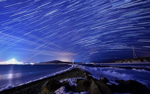 The Geminids meteor shower over Egersheld Cape on Russky Island in the Sea of Japan - Credit:  Yuri Smityuk