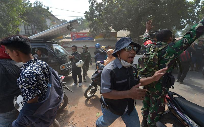 An Indonesian soldier and an official try to calm people shortly after an aftershock hits the area in Tanjung on Lombok island on August 9 - AFP