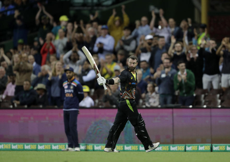 Australia's Matthew Wade raises his bat to acknowledge the applause from the crowd as he leaves the field after losing his wicket during the third T20 international cricket match between Australia and India at the Sydney Cricket Ground in Sydney, Australia, Tuesday, Dec. 8, 2020. (AP Photo/Rick Rycroft)