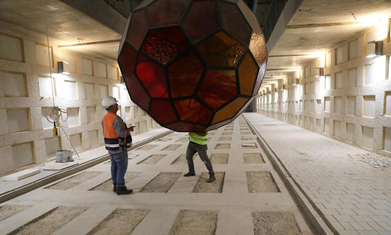 Labourers work with one of the Yvelle Gabriel-designed light fixtures as the cemetery's opening date approaches.