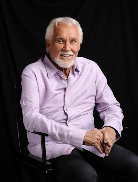 """FILE - In this Sept. 4, 2013 file photo, Kenny Rogers poses for a portrait at The Hot Seat in Nashville, Tenn. Rogers long ago cemented his legacy in the world of popular music, and we'll get another reminder of this on Sunday, Oct. 27, 2013, when he's finally inducted into the Country Music Hall of Fame with Bobby Bare and the late """"Cowboy"""" Jack Clement. Many believe Rogers' induction is years late since few did as much to spread country music beyond its once rural borders. (Photo by Donn Jones/Invision/AP, File)"""