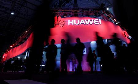 FILE PHOTO - Visitors walk past Huawei's booth during Mobile World Congress in Barcelona