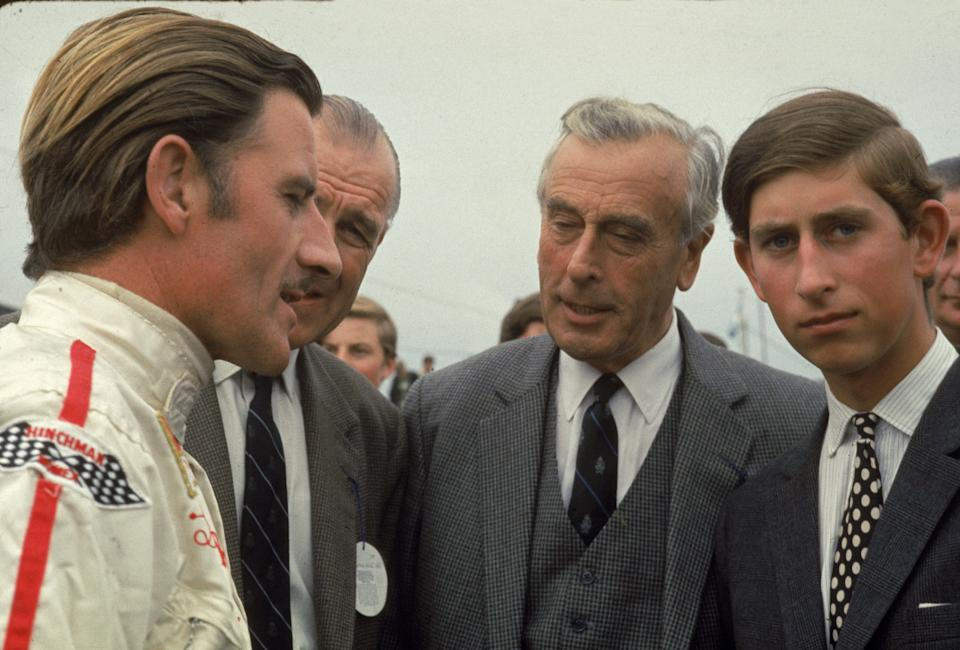 British race car driver Graham Hill talks with Lord Louis Mountbatten (1900 - 1979) and Prince Charles, Prince of Wales. (Photo by Susan Wood/Getty Images)