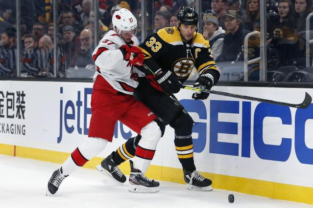 Carolina Hurricanes' Andrei Svechnikov (37) and Boston Bruins' Zdeno Chara (33) compete for the puck during the first period of an NHL hockey game in Boston, Tuesday, Dec. 3, 2019. (AP Photo/Michael Dwyer)