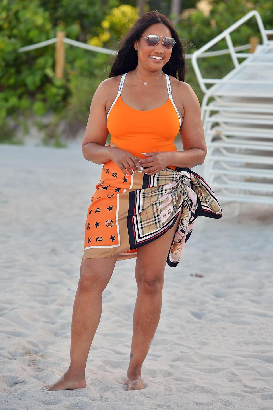 <p>Garcelle Beauvais soaks up some sun in an orange swimsuit at the beach on July 16 in Miami. </p>