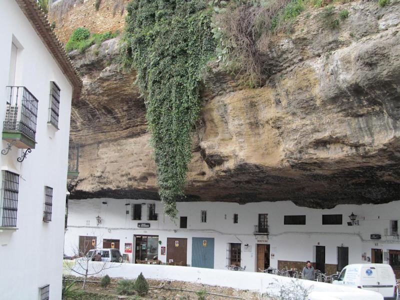 """This Jan. 17, 2013 photo shows the narrow road of Setenil de las Bodegas. Many of the houses and stores in this Spanish """"pueblo blanco,"""" or white village, are carved into river-eroded rock. (AP Photo/Giovanna Dell'Orto)"""