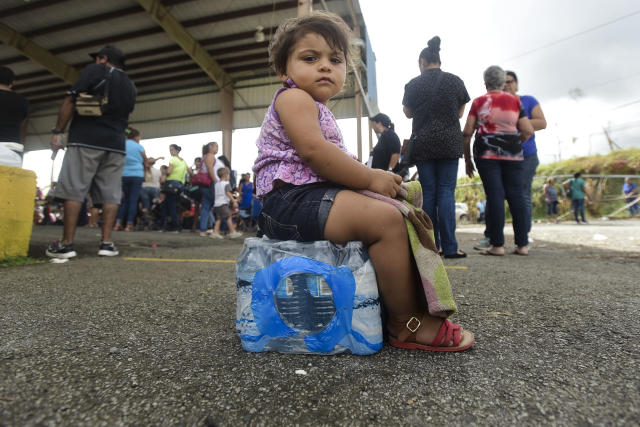 <p>Kerialys Aldea de Jesus sits on bottled water at the Jose de Diego Elementary School where residents file FEMA forms for federal aid in the aftermath of Hurricane Maria in Las Piedras, Puerto Rico, Monday, Oct. 2, 2017. Even those happy with the federal aid effort for the U.S. territory's 3.4 million people said they resented President Donald Trump's tweets about some Puerto Ricans being lazy and ungrateful. (Photo: Carlos Giusti/AP) </p>