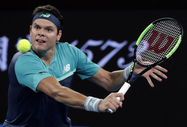 Canada's Milos Raonic plays a backhand return to Australia's Nick Kyrgios during their first round match at the Australian Open tennis championships in Melbourne, Australia, Tuesday, Jan. 15, 2019. (AP Photo/Aaron Favila)
