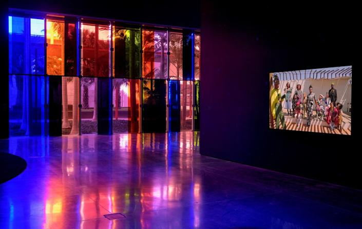 A film plays in a darkened room on a screen on a wall near colored windows.