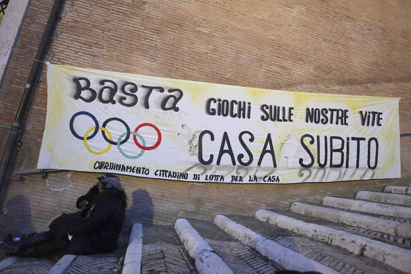 """A banner displayng the Olympic Games five-ring logo reads in Italian: """"Enough of games on our lives. Home now"""" in Rome's Capitol Hill Tuesday, Feb.14, 2012, during a demonstration for the right to housing. Premier Monti has scrapped Rome's bid for the 2020 Olympics, saying the government can't supply the required financial backing at a time of financial crisis. Premier Mario Monti announced after a Cabinet meeting Tuesday that it would be an irresponsible use of taxpayer money to fund the Olympic project. Costs for hosting the Olympics in Rome are estimated at $12.5 billion. The decision came a day before the deadline for formal submission of bid files to the International Olympic Committee.  (AP Photo/Mauro Scrobogna, LaPresse) ITALY OUT"""