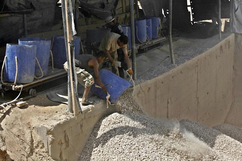 Palestinian workers unload gravel being pulled from a smuggling tunnel along the border between the Gaza Strip and Egypt, in Rafah, southern Gaza Strip, Wednesday, July 24, 2013. Egypt has sealed smuggling tunnels and blocked most passenger traffic in the toughest border restrictions on the Gaza Strip in recent years, causing millions of dollars in economic losses and prompting concerns among Gaza's Hamas rulers that the territory is being swept up in the Egyptian military's crackdown on Islamic fundamentalists. (AP Photo/Adel Hana)