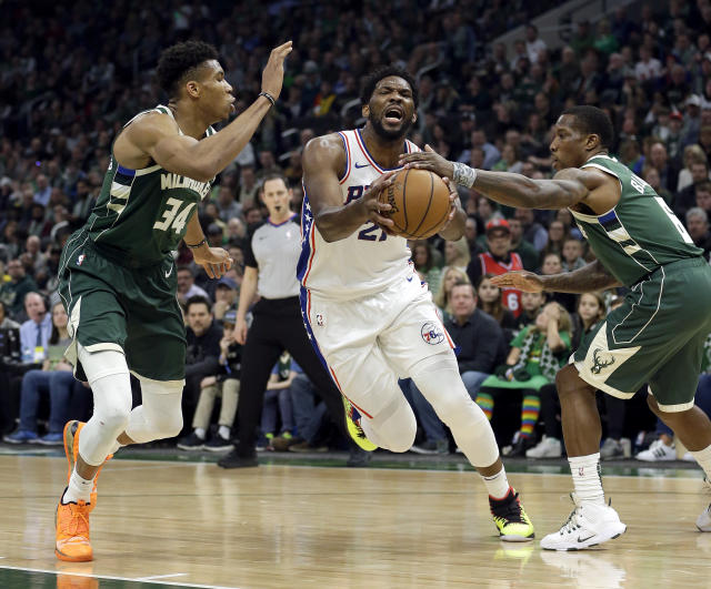 Philadelphia 76ers' Joel Embiid drives between Milwaukee Bucks' Giannis Antetokounmpo (34) and Eric Bledsoe (6) during the first half of an NBA basketball game Sunday, March 17, 2019, in Milwaukee. (AP Photo/Aaron Gash)