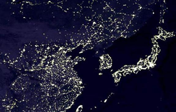 North Korea looks dark by night compared to brightly-lit South Korea on the Korean peninsula (between China on the left and Japan on the right).