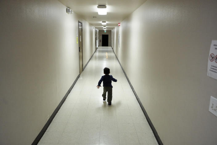 FILE - In this Dec. 11, 2018 file photo, an asylum-seeking boy from Central America runs down a hallway after arriving from an immigration detention center to a shelter in San Diego. The federal government may house unaccompanied migrant children on a California Army National Guard base in central California, officials said. The Pentagon on Friday, April 2, 2021, approved the use of Camp Roberts to temporarily house children traveling alone, according to a defense official. (AP Photo/Gregory Bull, File)