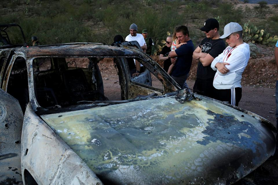 Relatives of slain members of Mexican-American families belonging to Mormon communities observe the burnt wreckage of a vehicle where some of their relatives died, in Bavispe, Sonora state, Mexico November 5, 2019. REUTERS/Jose Luis Gonzalez