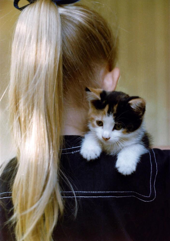A girl with blond hair carries a calico kitten. (Sally Reeder)