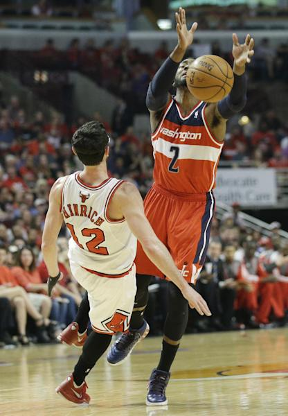 Chicago Bulls guard Kirk Hinrich (12) fouls Washington Wizards guard John Wall (2) during the first half in Game 1 of an opening-round NBA basketball playoff series in Chicago, Sunday, April 20, 2014. (AP Photo/Nam Y. Huh)